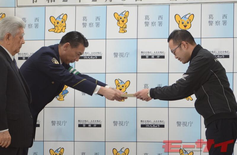 委嘱状を手渡す葛西警察署署長、半田正浩さん(左奥)と受け取るホンダドリーム葛西店店長、平野浩久さん。